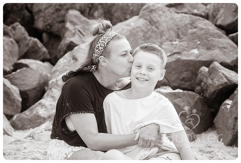 Mum kissing son at the beach