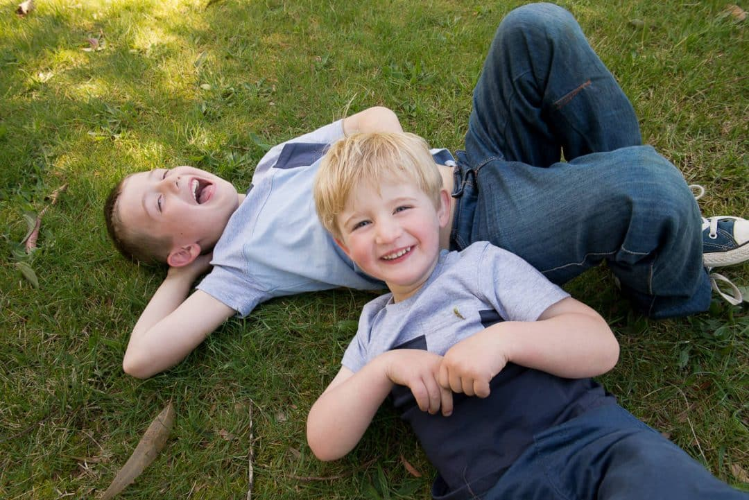 Brothers lying on the grass