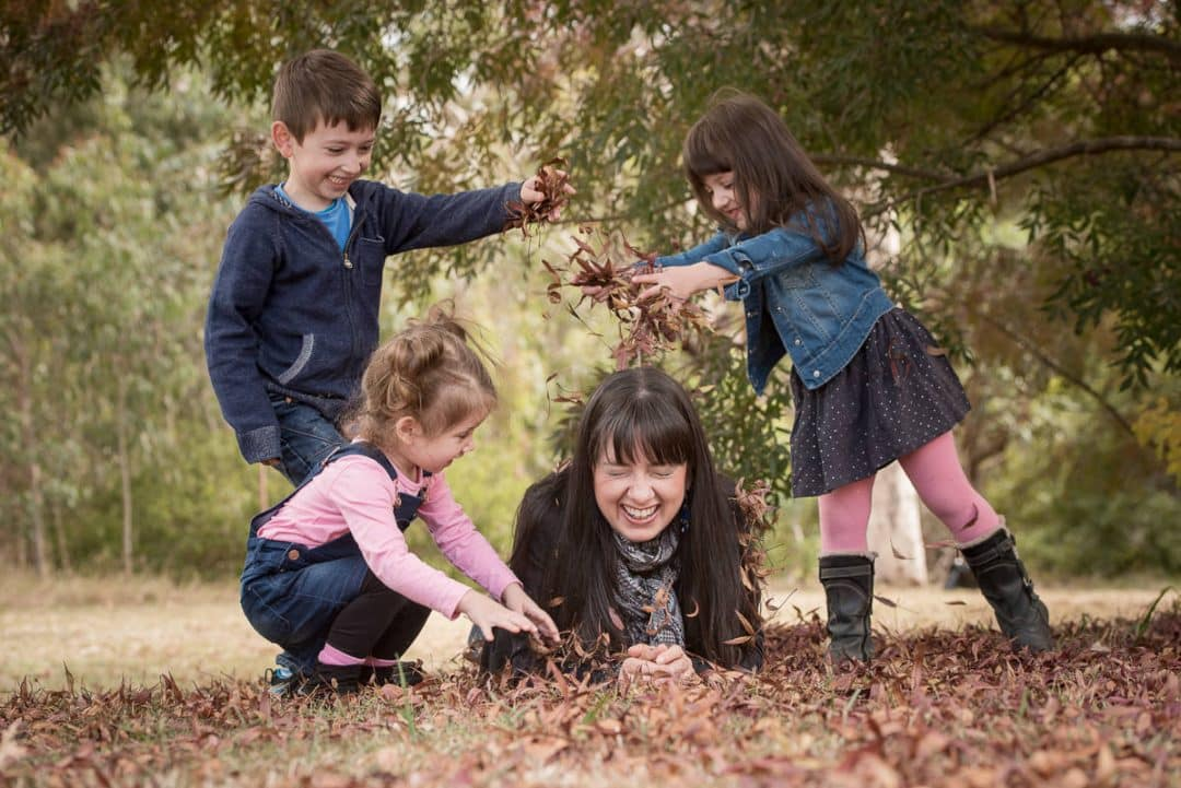 Kids and mum playing with leaves